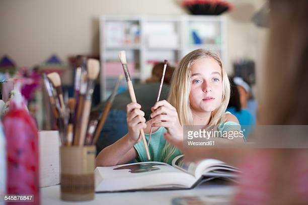 Girl in arts class holding brushes