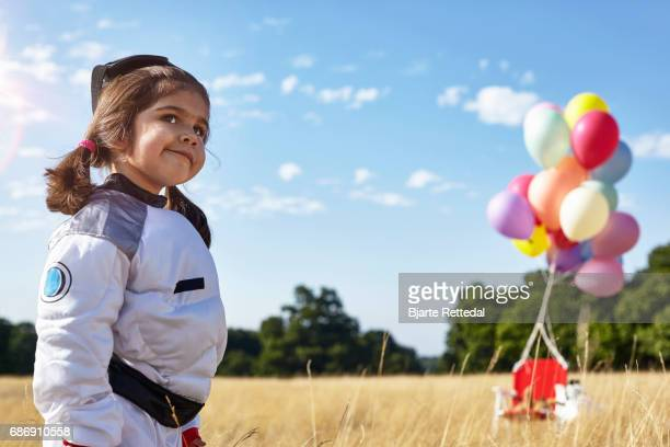 Girl in Astronaut Suit looking sly in front of her space vehicle