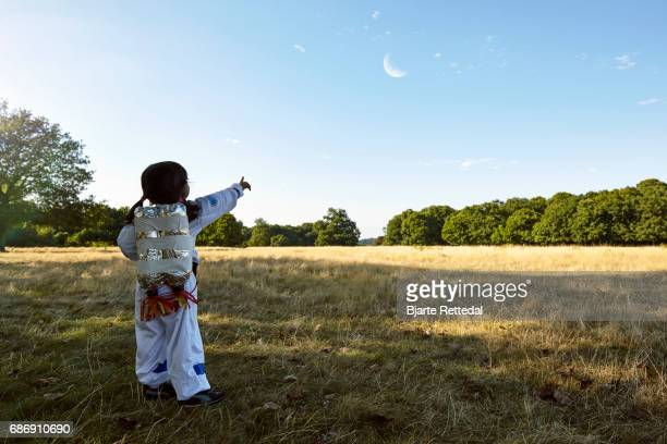Girl in Astronaut Suit pointing towards the moon