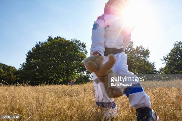 Girl in Astronaut Suit running through field