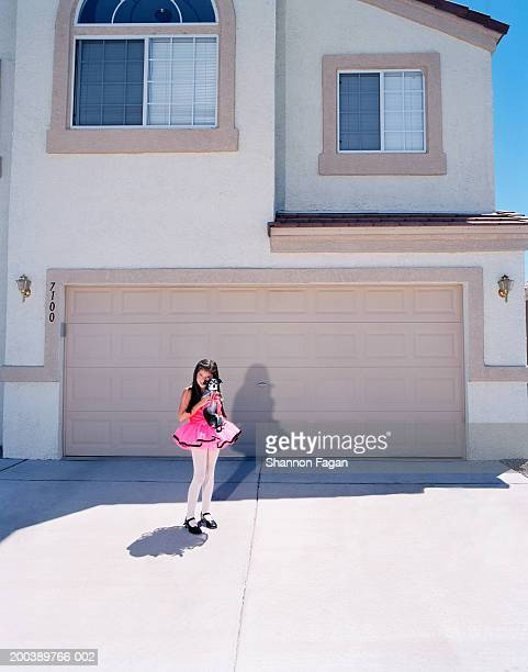 Girl (7-9) in ballerina costume holding dog in driveway, portrait