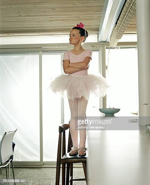 Girl (7-9) in ballet costume standing on chair