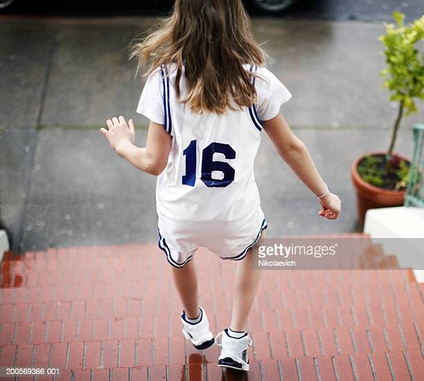 Girl (10-11) in basketball uniform running down stairs, rear view