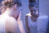 Worried girl standing in front of mirror