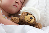 Young girl poorly in bad cuddling her teddy who also feels poorly.