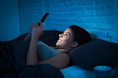 young beautiful womanl in bed using mobile phone late at night at dark bedroom lying happy and relaxed enjoying social media network at her phone in communication internet addiction concept