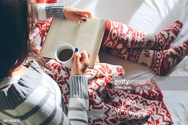 Girl in bed with coffee cup reading a book