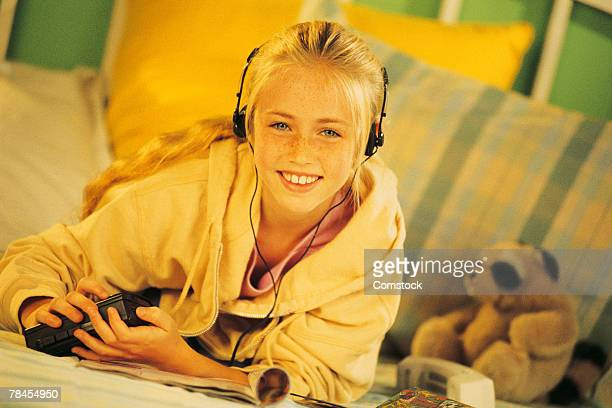 Girl in bedroom listening to music with headphones