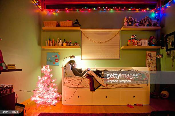 girl in bedroom with laptop & pink Christmas tree