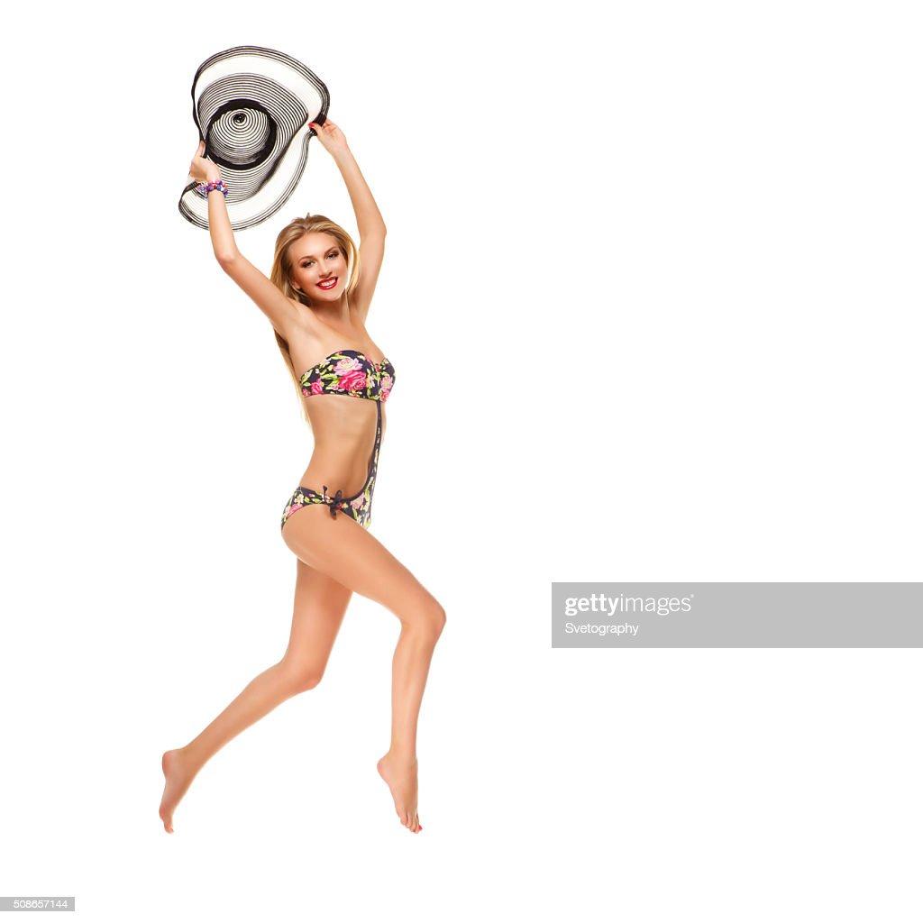 Girl in bikini holding summer hat : Stock Photo