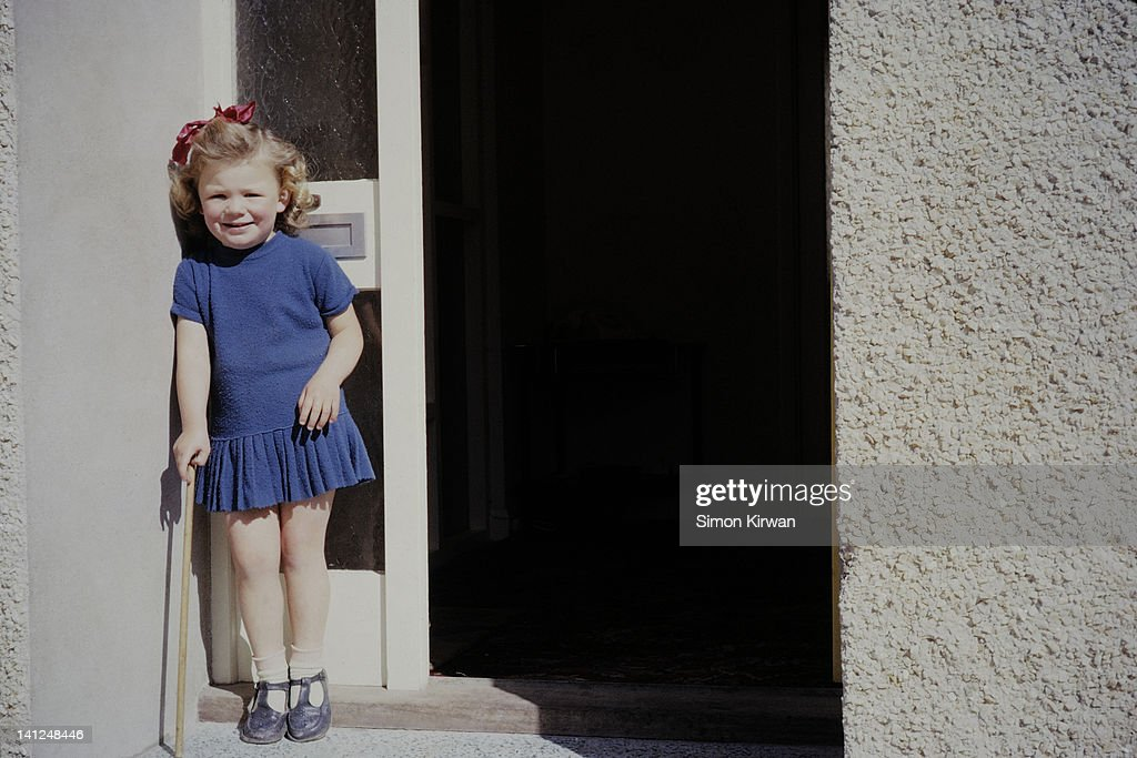 Girl in blue dress standing in doorway : Stock Photo