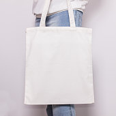 Girl in blue jeans holds blank cotton eco tote bag, design mockup. Handmade shopping bag for girls.