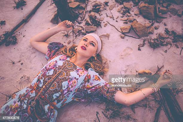 Girl in boho fashion lying down on sand