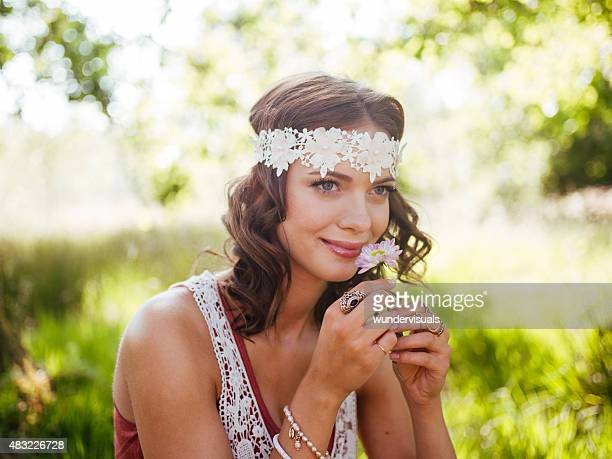 Girl in boho fashion smelling a flower in summer park