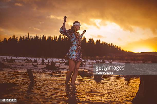 Girl in boho fashion standing in water at sunset
