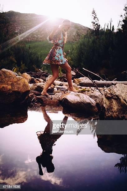 Fille en robe fleuri de style bohème sur des pierres de gué de lac