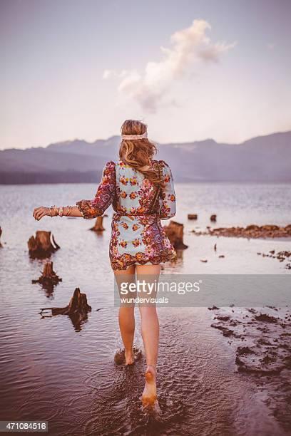 Girl in boho floral dress walking through a natural lake