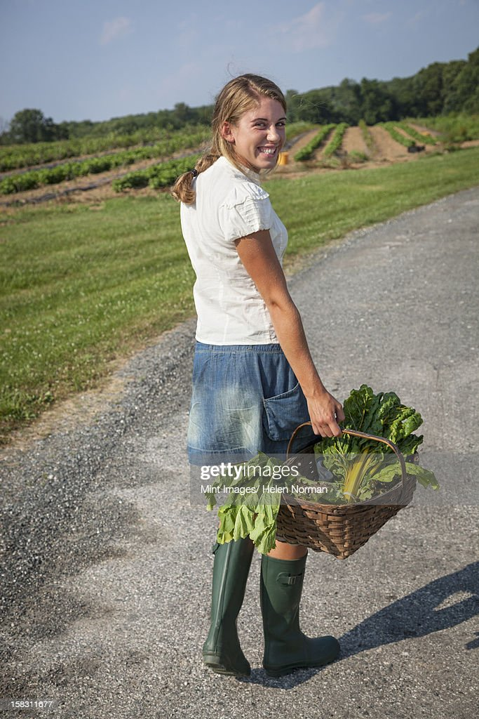 A girl in boots on a farm carrying a basket full of fresh produce. : Stock Photo