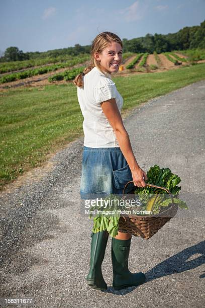 A girl in boots on a farm carrying a basket full of fresh produce.