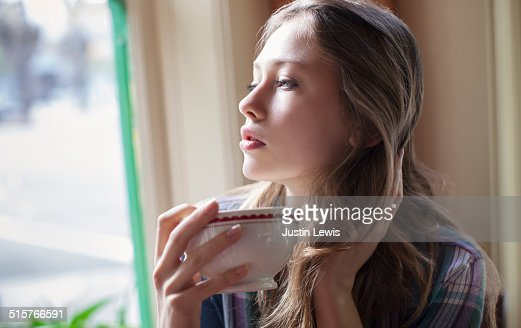Girl in cafe drinking tea and thinking