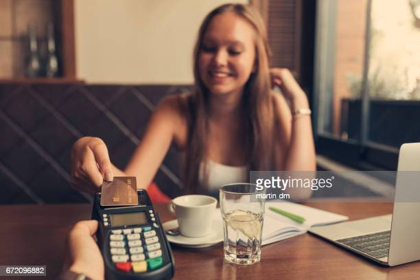 Girl in cafe paying contactless with credit card