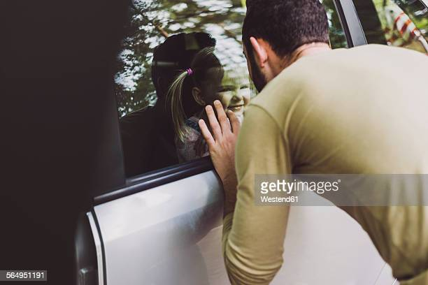 Girl in car looking at father behind window pane