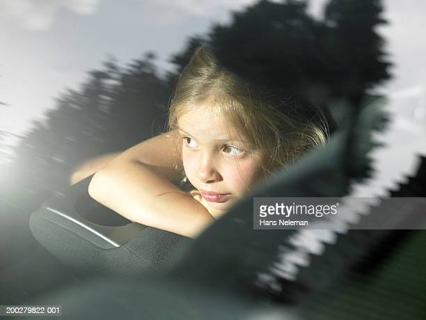 Girl (6-8) in car looking out window, close-up