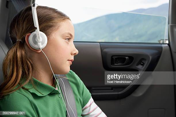 Girl (6-8 years) in car wearing headphones, close-up, side view