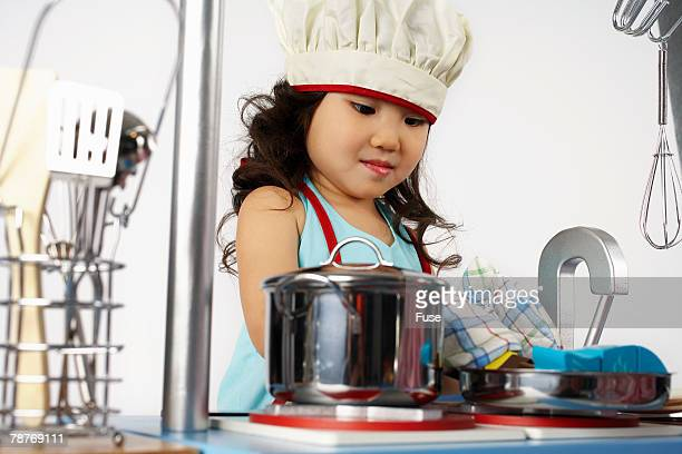 Girl in Chefs Hat Pretending to Cook a Fish