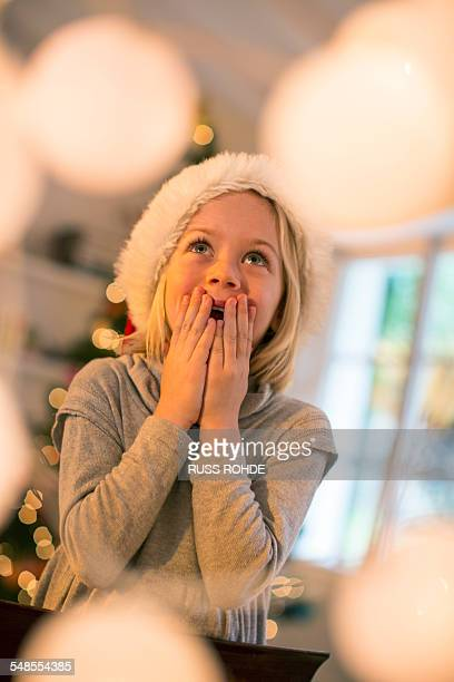 Girl in Christmas hat looking up in awe