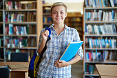 Attractive student looking at camera in library
