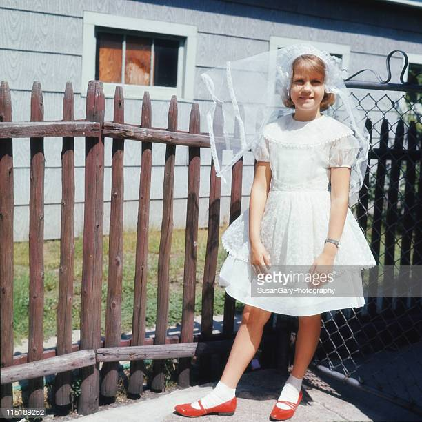 Girl in communion dress and red shoes