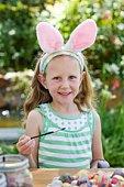 Girl in costume decorating Easter eggs