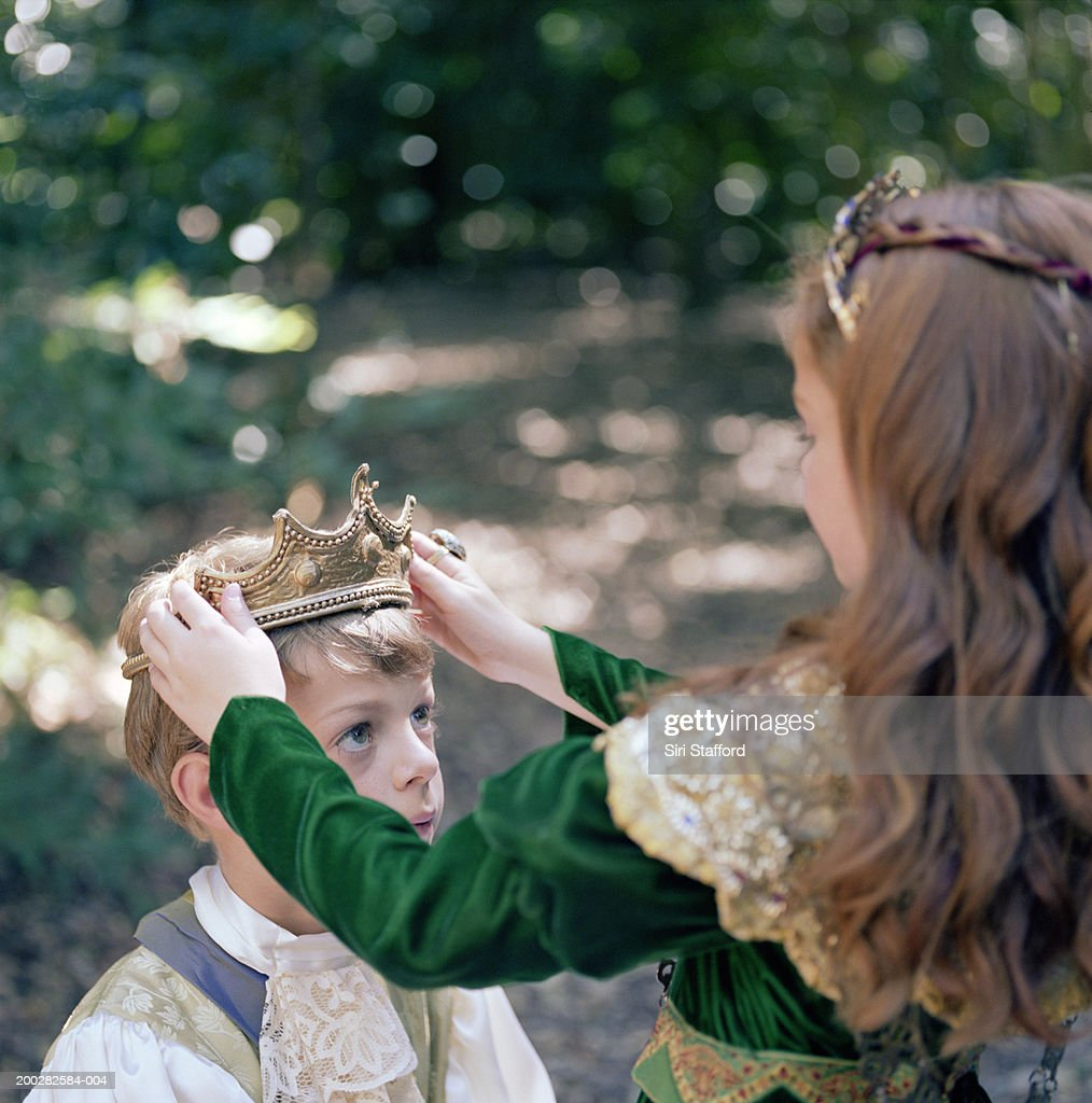 Girl (8-10) in costume putting crown on boy's head : Stock Photo