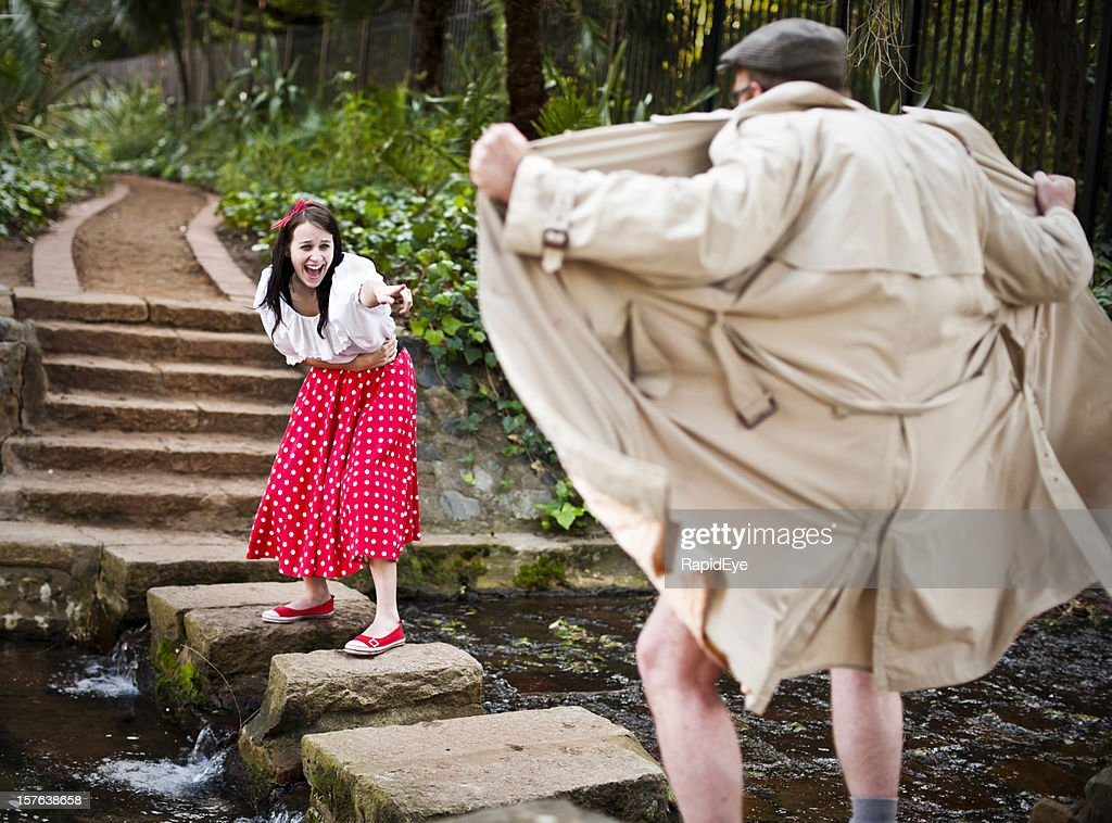 Girl in cute outfit laughs at raincoat clad flasher : Stock Photo