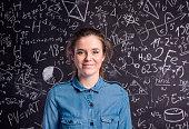 Teenage girl in blue denim shirt against big blackboard with mathematical symbols and formulas. Studio shot on black background.
