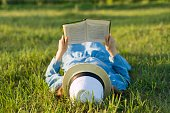Girl in dress and hat lies on green grass reading book. View from above.