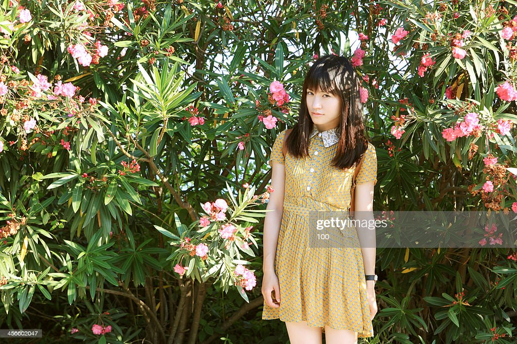 Girl in dress standing in front of flowers : Stock Photo