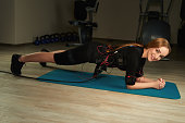 Blonde girl in Electrical Muscular Stimulation suit doing plank exercise in gym