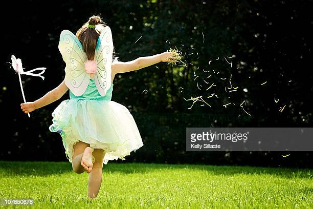 A girl in fairy costume running and thowing grass