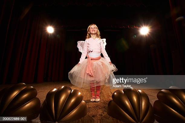 Girl (6-10) in fairy costume standing on stage, looking up, smiling