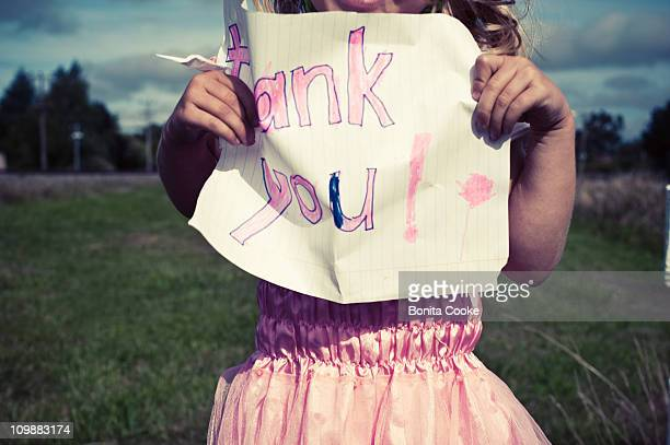 Girl in fairy dress holding 'thank you' sign