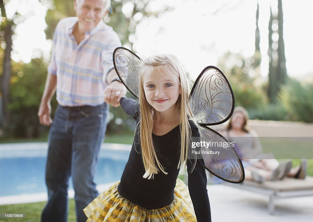 Girl in fairy wings pulling grandfather along : Stock Photo
