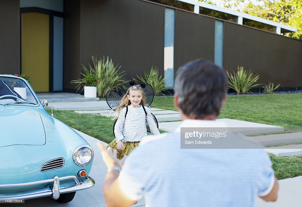 Girl in fairy wings running to father : Stock Photo