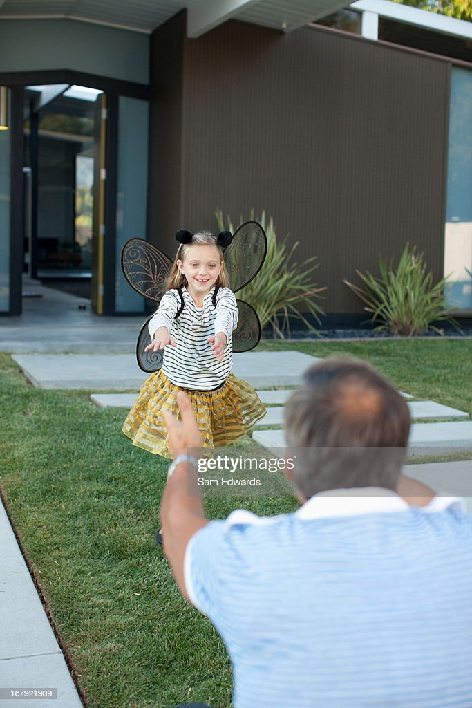 Girl in fairy wings running to father