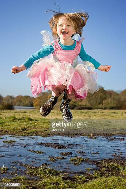 Girl in fancy dress costume jumping in muddy puddle