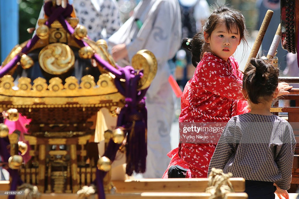 A girl in festival outfit plays with a drum as her group takes a break next to a portable shrine or mikoshi during the Sanja Festival at the Asakusa...