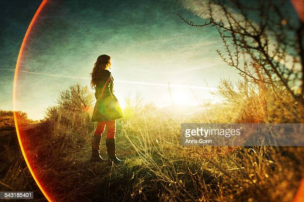 Girl in field looking at sunset, lens flare rings