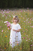 Girl in field of flowers with bouquet