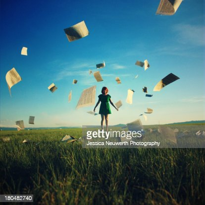 Girl in field surrounded by book pages : Stock Photo